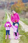 Mother and her daughters in autumnal nature with apples — Stock Photo