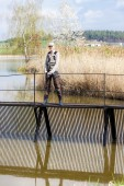 Woman fishing on pier at pond — Stock Photo