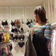 Young woman chooses a bra in lingerie store — Stock Video #54945775