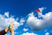 Hands holding kite — Stock Photo