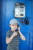 Boy speaking by the street telephone — Stock Photo
