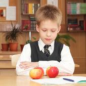 Boy with apples in a classroom — Zdjęcie stockowe