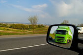 Green, a moving truck in the reflection of the mirror associated — Stock Photo