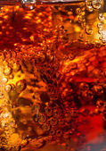 Cola in glass with ice and a bubbles of gas. — Stock Photo