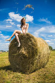 Young woman sit on a newly built hay stack. — Stock Photo