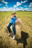 Young couple sitting on a hay stack — Stock Photo