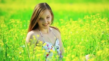 Happy teen on the meadow with yellow flowers — Stock Video
