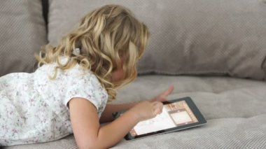 Little girl on couch playing on the tablet pc — Stock Video