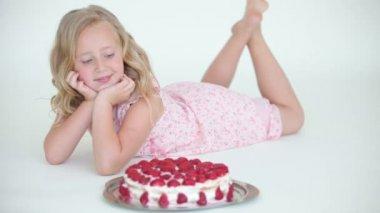 横になっている、イチゴのケーキを賞賛の女の子 — ストックビデオ