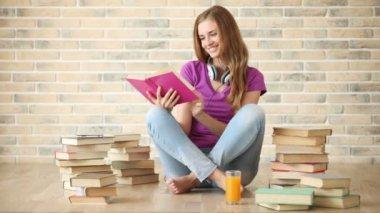 Flicka sitter på golvet läser bok — Stockvideo