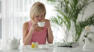 Woman sitting at table drinking tea — Stock Video