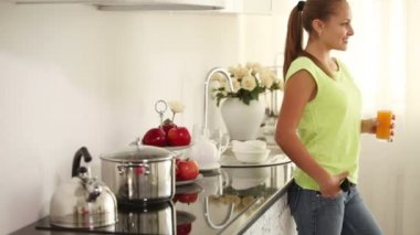Girl standing in kitchen holding glass — Stock Video