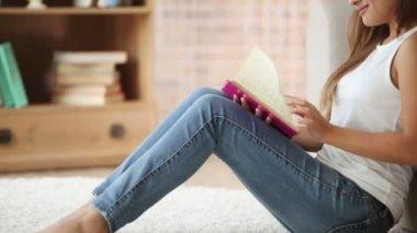 Girl sitting on floor  reading book — Stock Video