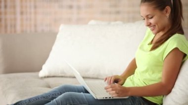 Cheerful girl sitting on sofa with laptop — Stock Video