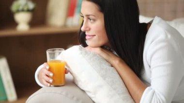 ジュースのグラスを持ってソファに女の子 — ストックビデオ