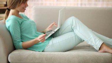 Flicka avkopplande soffan med laptop — Stockvideo