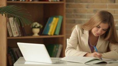 Söt flicka sitter på skrivbord skrift — Stockvideo