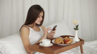 カップから飲むの携帯電話の使用女の子 — ストックビデオ