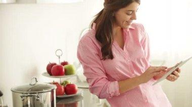 Flickan står i köket med pekplatta — Stockvideo