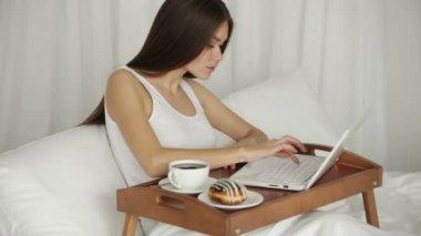 Kvinnan avkopplande i sängen med laptop — Stockvideo