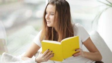 本を読んでのウィンドウで座っている女の子 — ストックビデオ