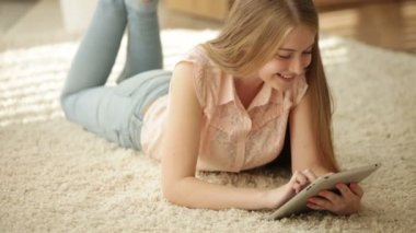 Girl lying on floor using touchpad — Stock Video