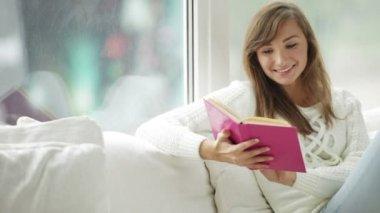 Flicka sitter vid fönster läser bok — Stockvideo