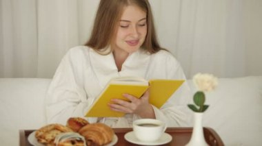 Girl with tray of food reading book — Stock Video