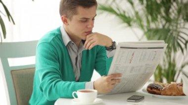 Homem sentado na mesa lendo jornal — Vídeo stock
