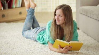 Girl lying on carpet reading book — Stock Video