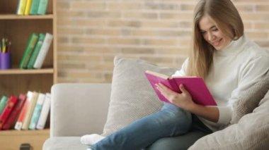 Ute flicka sitter på soffan läsa bok — Stockvideo