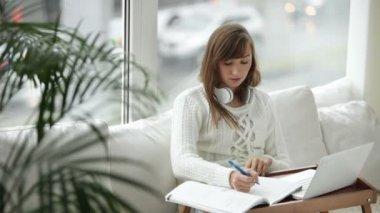 Attraktiva flicka skriver i anteckningsboken — Stockvideo