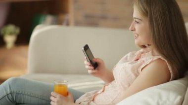 女の子のジュースを飲んでの携帯電話を使用して — ストックビデオ