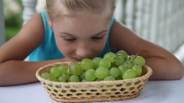 Little girl smelling grapes — Stock Video