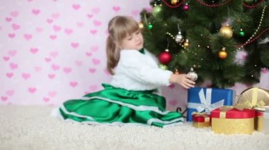 Girl sitting near a Christmas tree — Stock Video