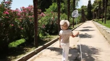 Girl walking with a butterfly net — Stock Video