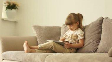 Meisje met tablet zittend op de Bank — Stockvideo