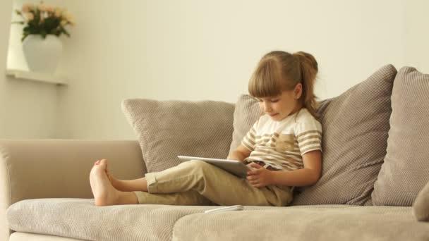 Chica con tablet sentado en el sofá — Vídeo de stock