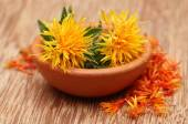 Safflowers in clay bowl — Stock Photo