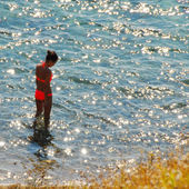 Girl in sunny sea water — Stock Photo