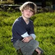 Young boy in garden looking over his shoulder — Stock Photo #62332443