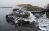Stones in the ice on the lake — Stock Photo