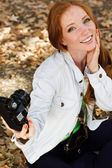 Nice girl photographer taking selfe in autumn park — Stock Photo