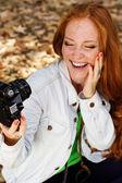 Nice girl photographer taking selfe in autumn park — Stock Photo