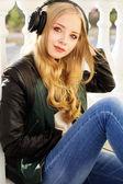 Jovem adolescente feliz está usando fones de ouvido — Fotografia Stock