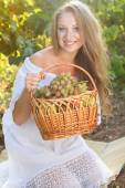 Portrait of young beautiful woman holding grapes — Stock Photo