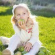 Child with green apples sitting on grass — Stock Photo #54653177