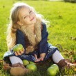 Child with green apples sitting on grass — Stock Photo #54653183