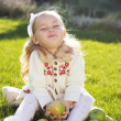 Child with green apples sitting on grass — Stock Photo #54653185