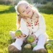Child with green apples sitting on grass — Stock Photo #54653193